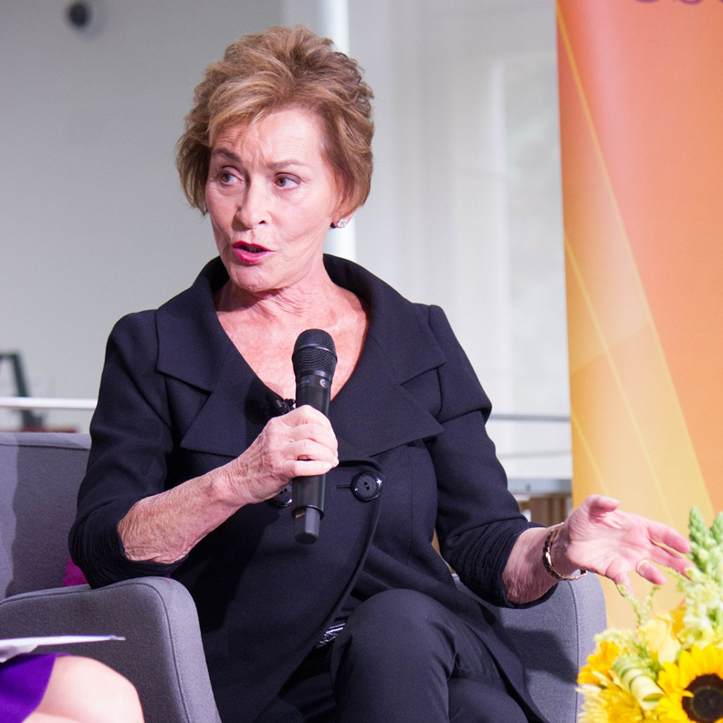 Judge Judy speaking holding a mic