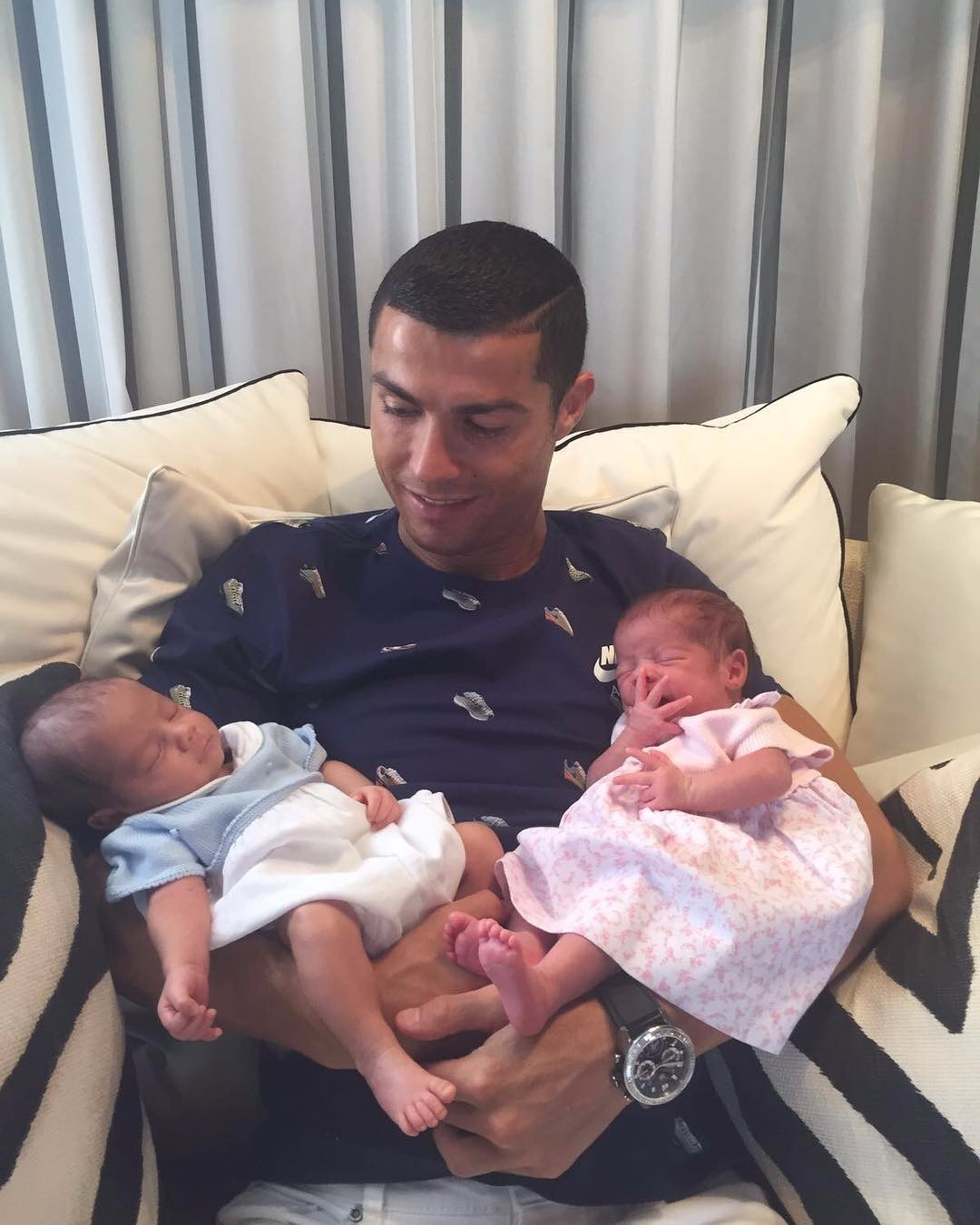 Cristiano Ronaldo holds his babies while sitting at a sofa.
