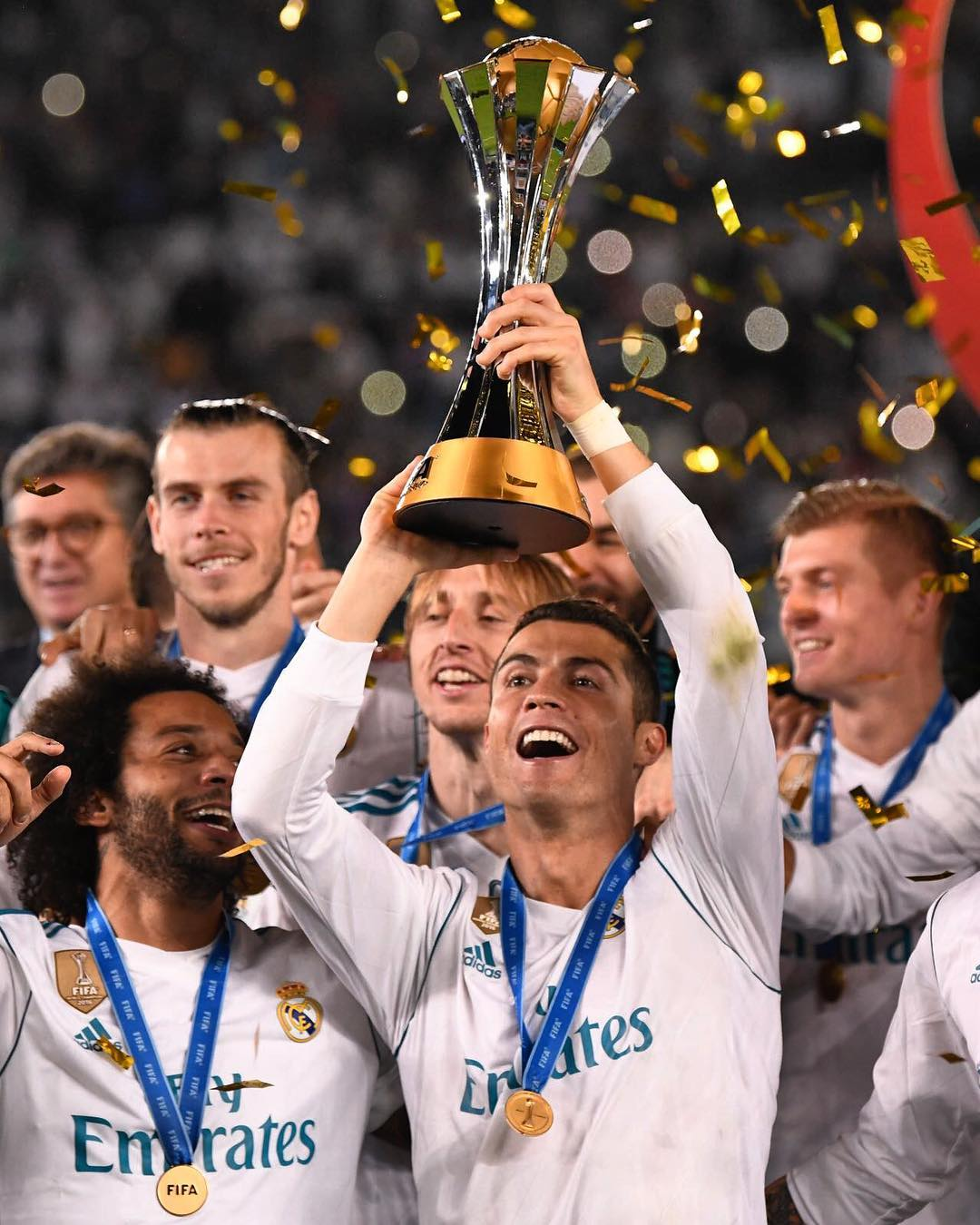 Cristiano Ronaldo is holding a trophy in his hand and his Real Madrid team rejoicing the win of FIFA Club World Cup 2017