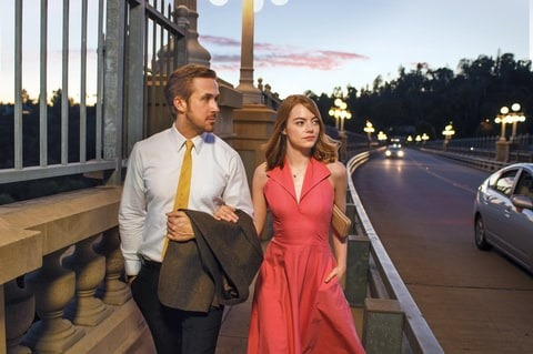 Emma Stone and Ryan Gosling walk through the streets as a couple for the movie La La Land. They're carrying a sizzler look which is best suited.