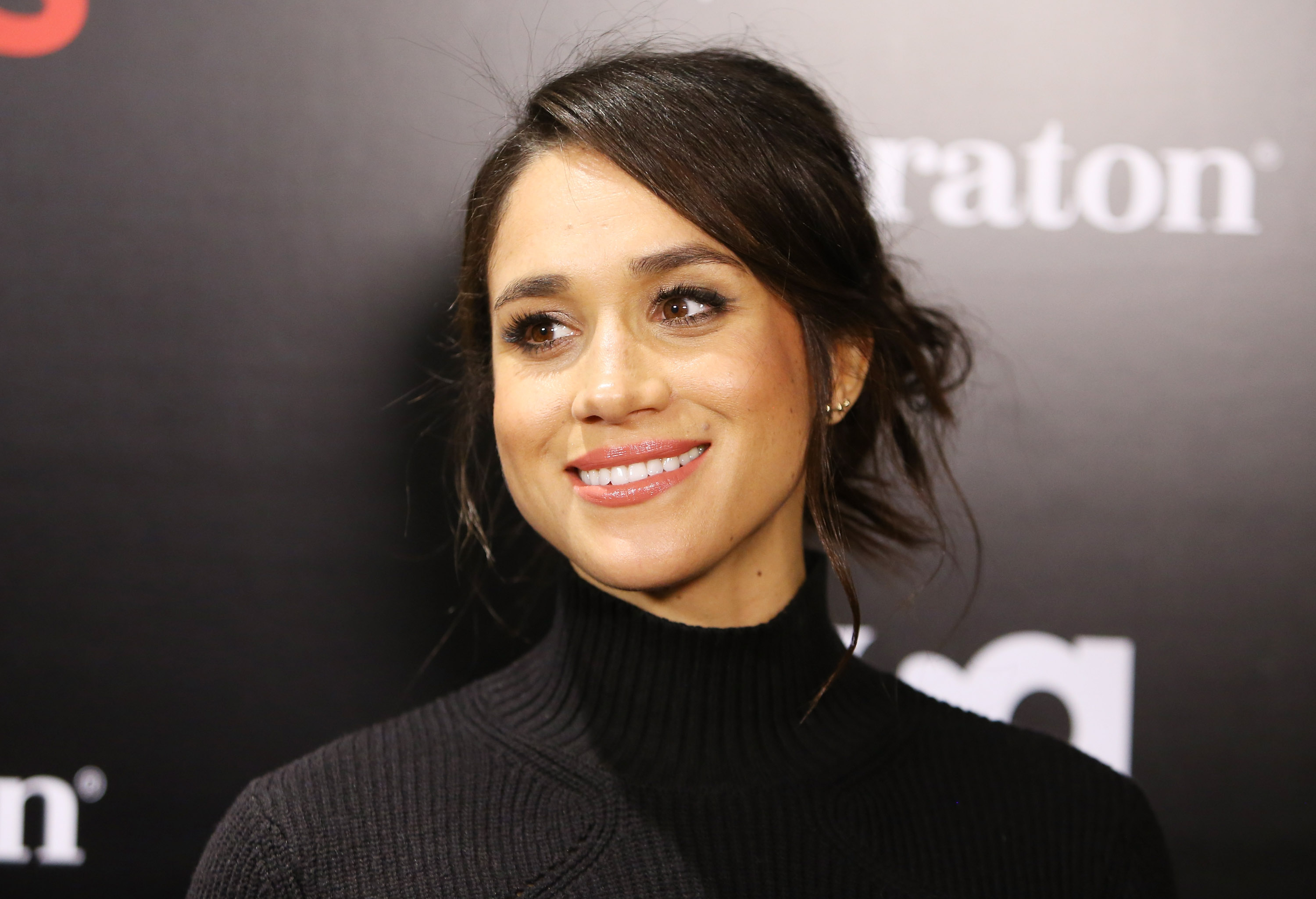 Meghan Markle poses for a picture at an event in a black dress
