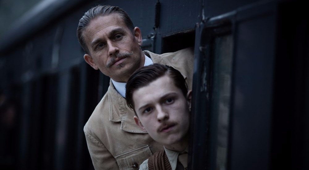 Still from The Lost City of  Z, Tom Holland with mustache, Charlie Hunnam is behind Holland