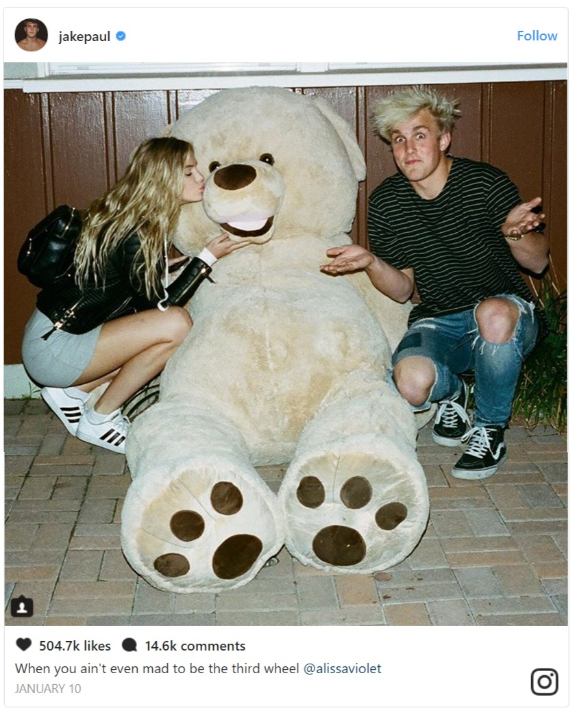 Jake Paul and Alissa Violet crouching on the floor, there's a life size teddy bear between them and Alissa is kissing it