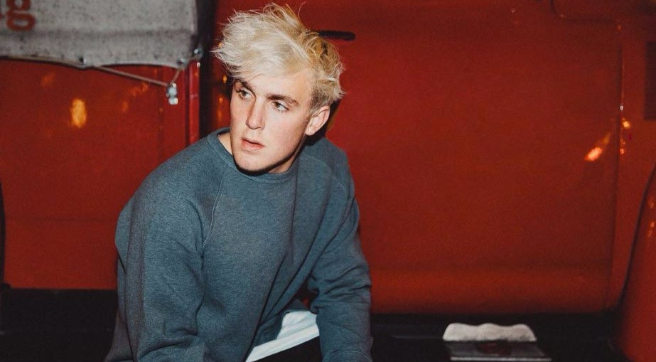 Blonde haired Jake Paul, wearing a grey sweatshirt, sitting in front of a red colored vehicle
