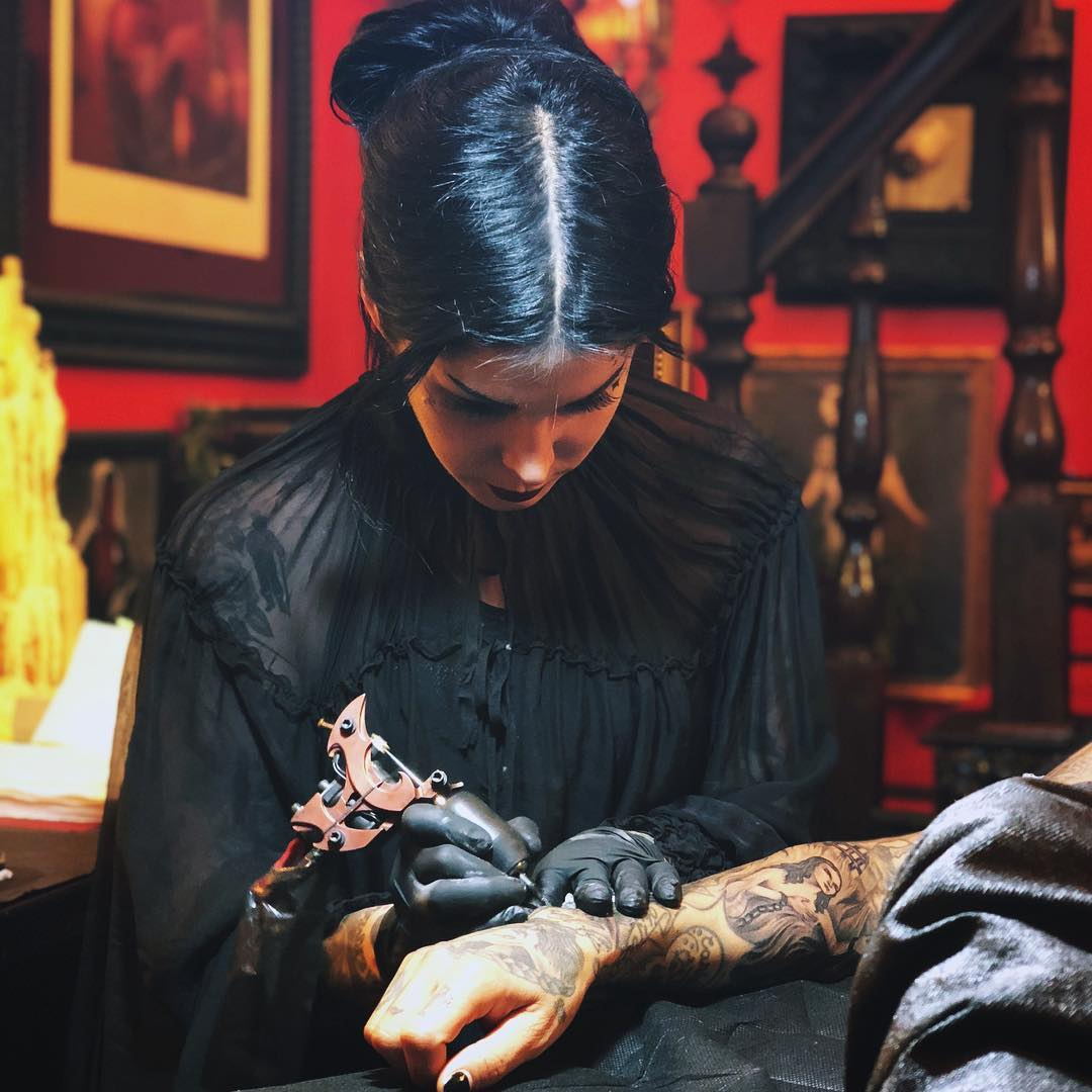 Kat Von D tattooing on a person's hand