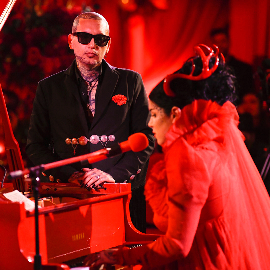 Kat Von D is playing piano while her husband, Rafael Reyes is looking at her