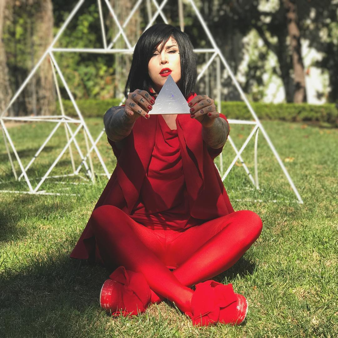 Kat Von D is holding a triangle in her hands wearing entire red attire