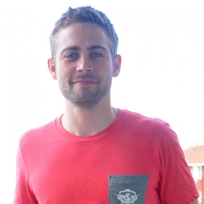 Cody Walker is facing the camera with subtle smile. He is wearing red t-shirt. He is the younger brother of Paul Walker,
