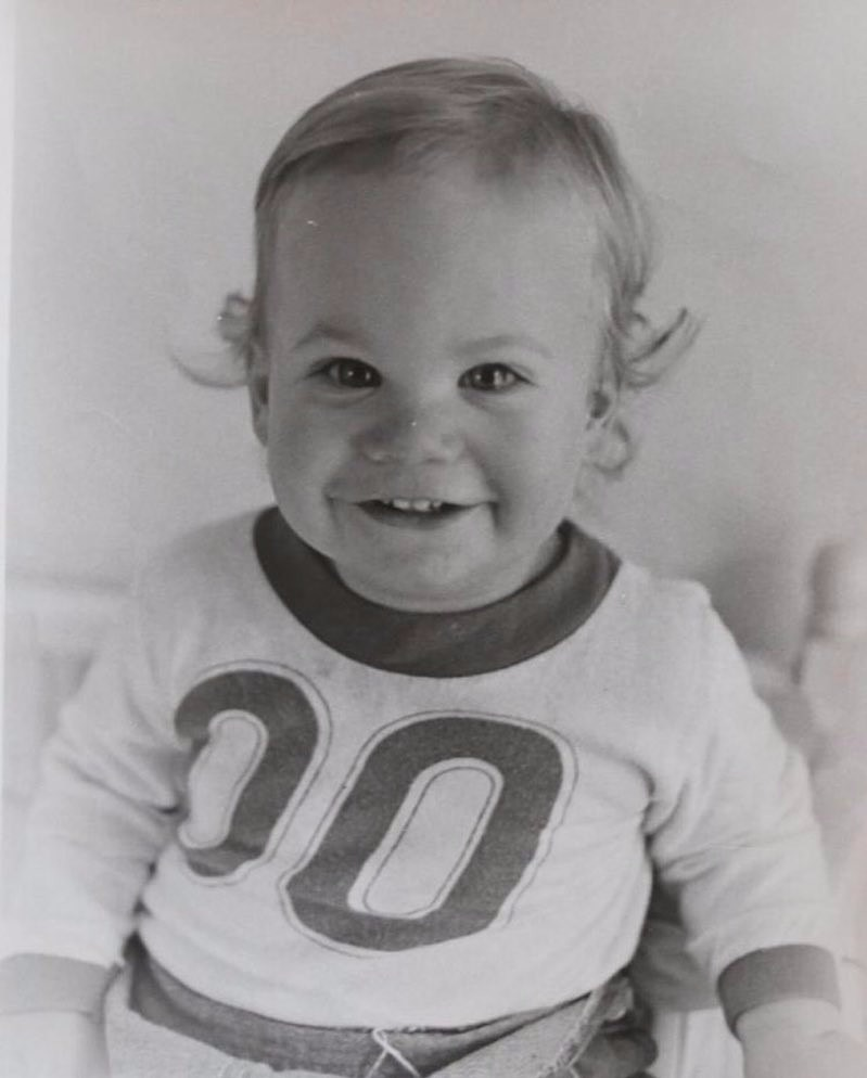 Black and white image of baby Paul Walker smiling at the camera. He is wearing a tee-shirt with double zero.