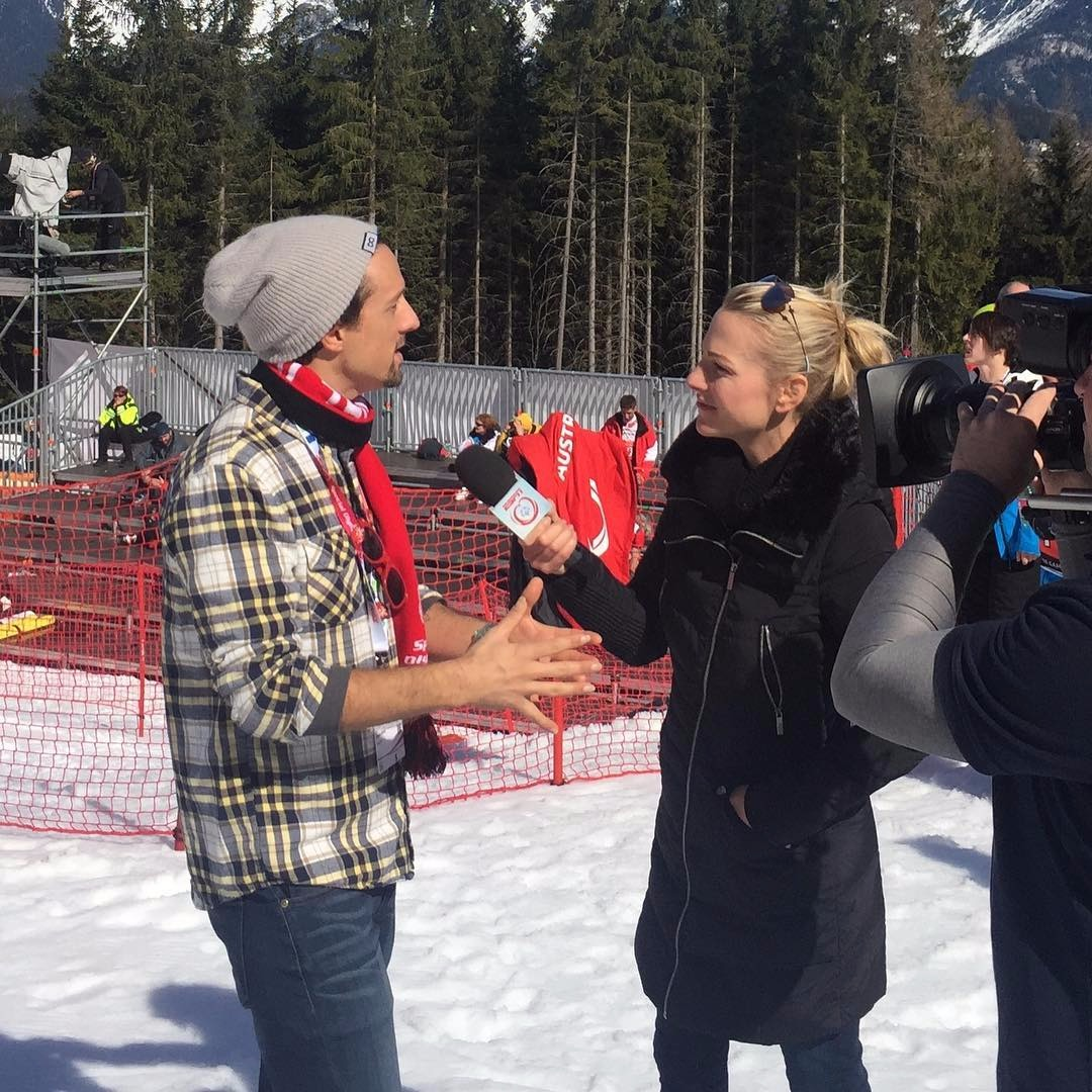 Lindsay Czarniak interviewing Jason Mraz in a snowy surrounding. Jason is using hand gestures to explain his point.