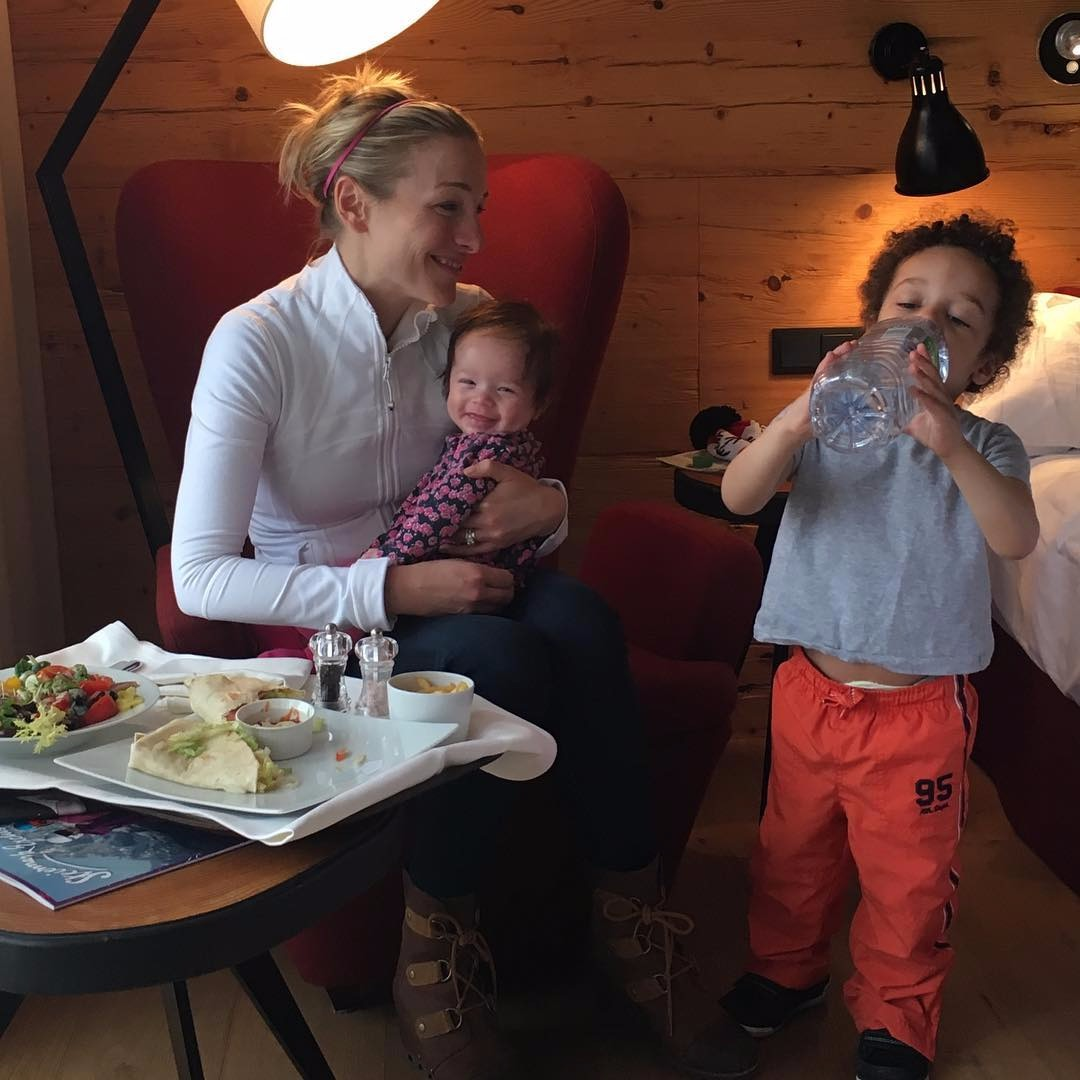 Lindsay Czarniak looking at her son Delano with love while he is drinking water. She holds her daughter Sibby by her arms. They are having the perfect mother children time.