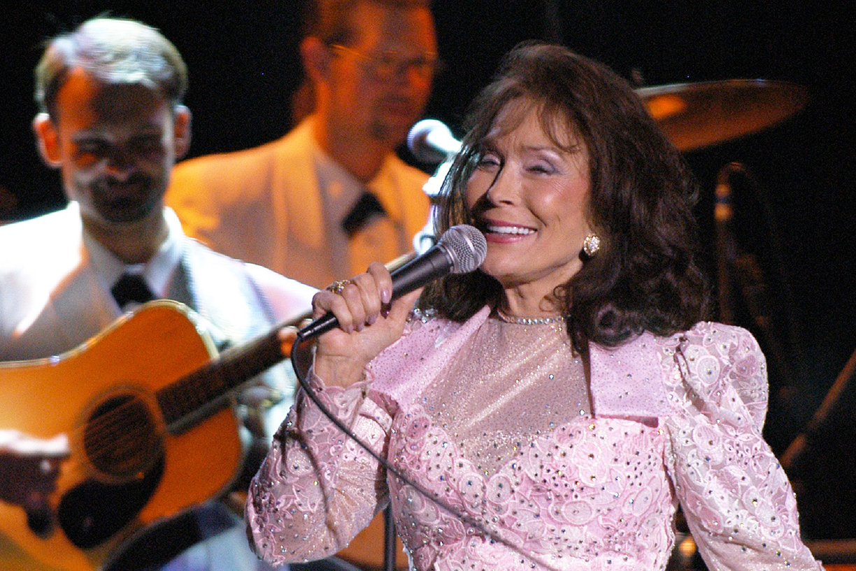 Loretta Lynn singing in a show. There are some music artits behind her