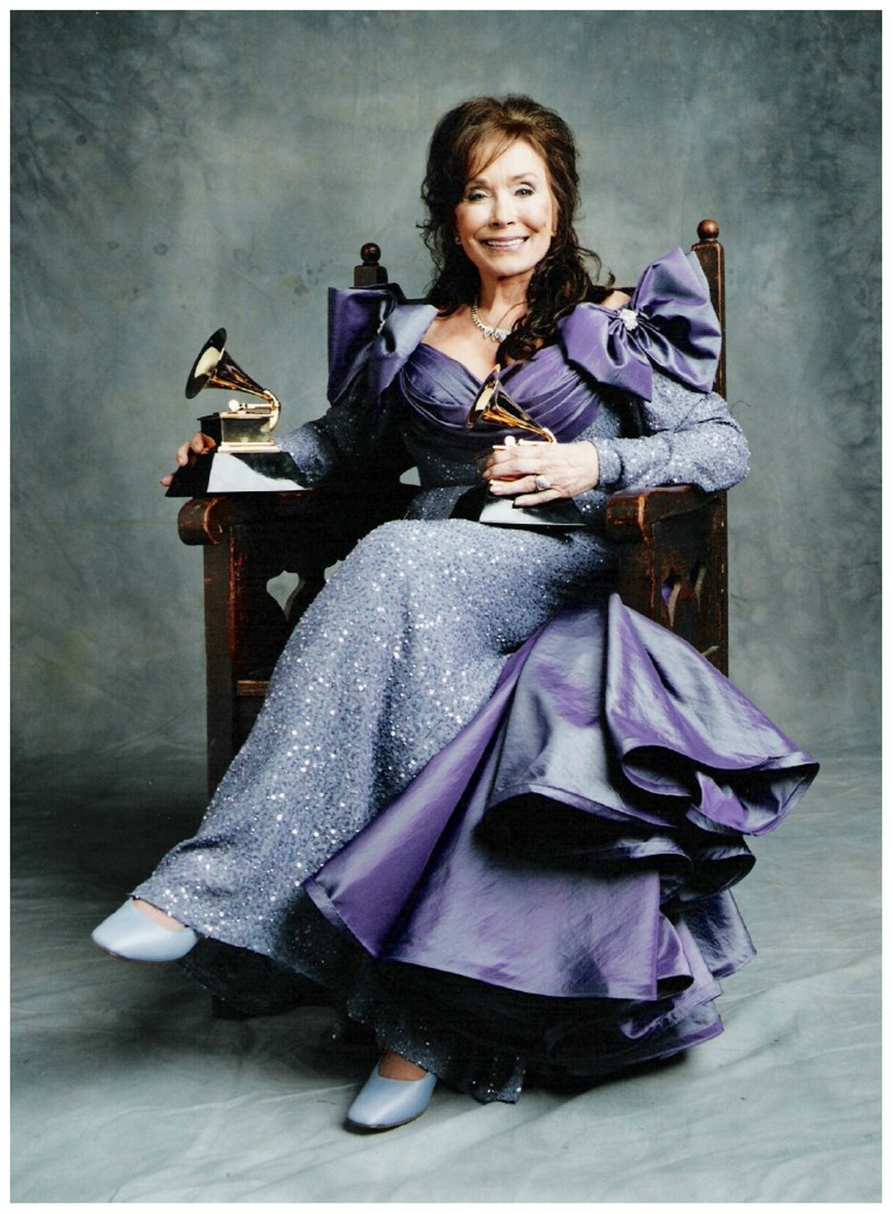 Loretta Lynn giving royal pose with her awards