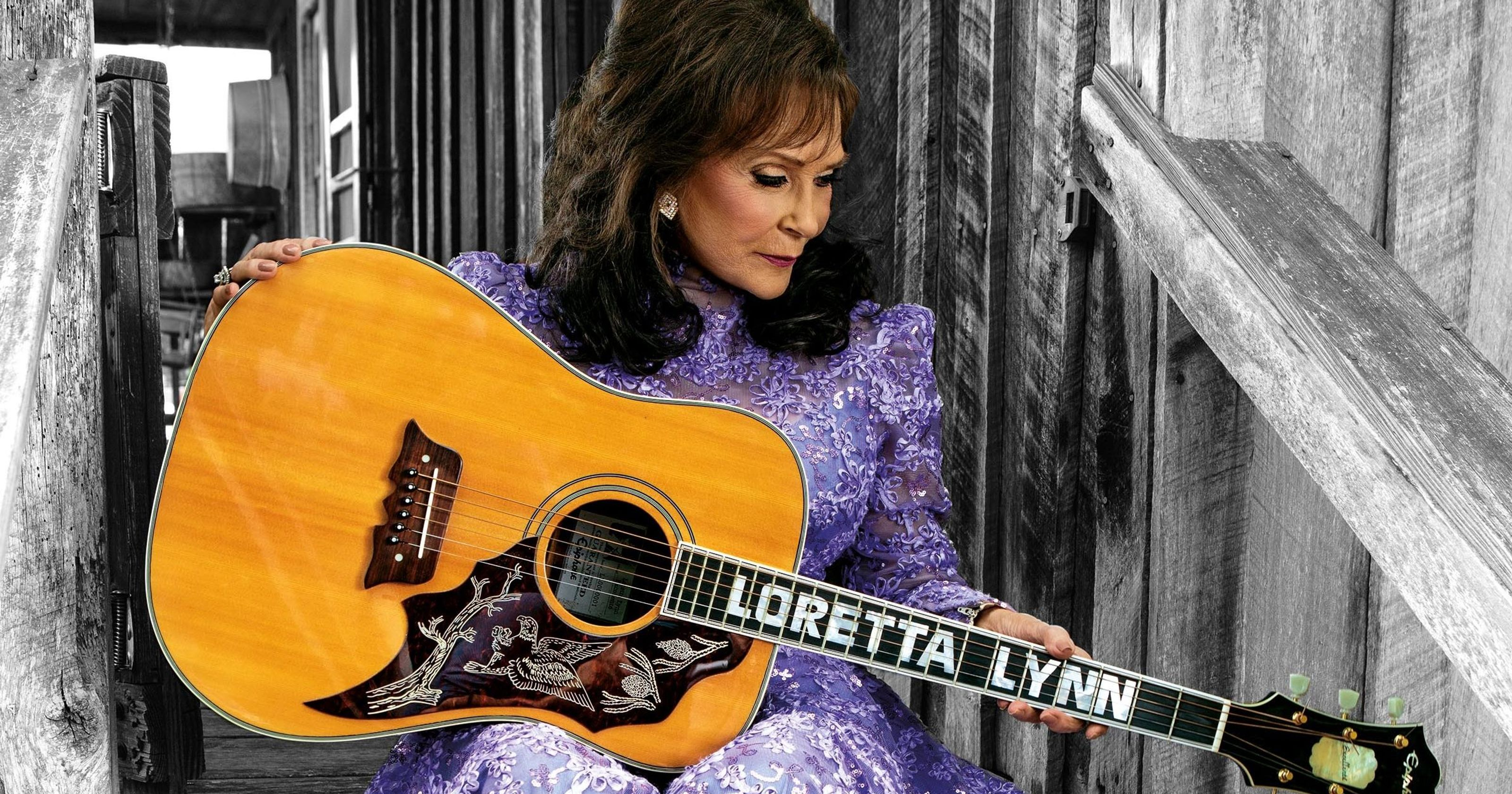 Loretta Lynn holding guitar with her name on the guitar