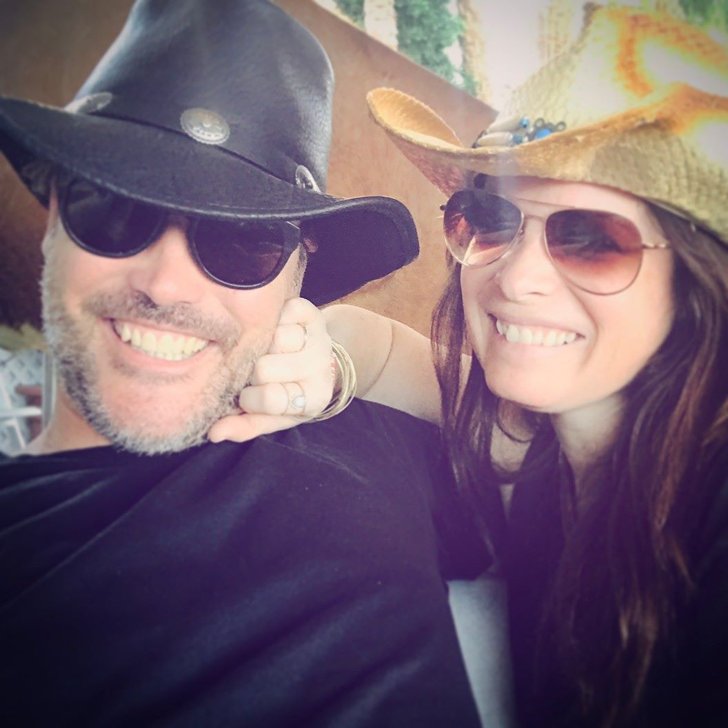 Holly Marie Combs touching cheek of boyfriend Mike, they're both wearing sunglasses and cowboy hats