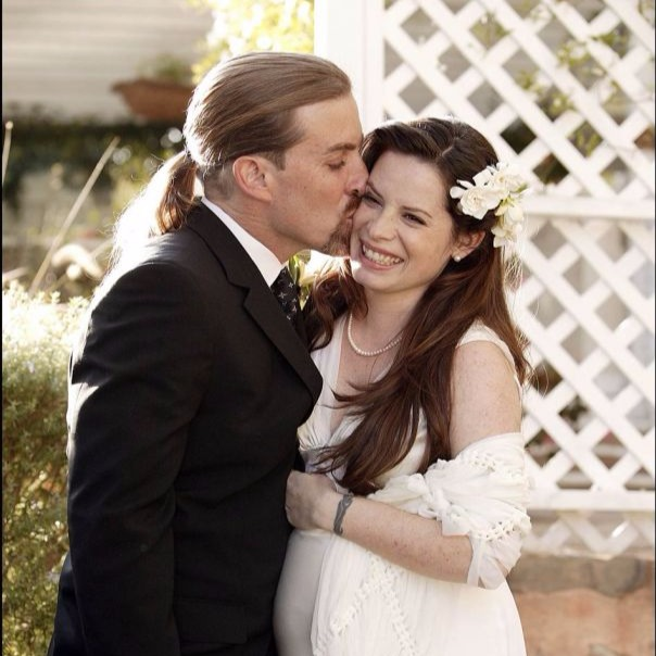 Holly Marie Combs in her wedding dress, her now ex husband, David Donoho, kissing her on cheek