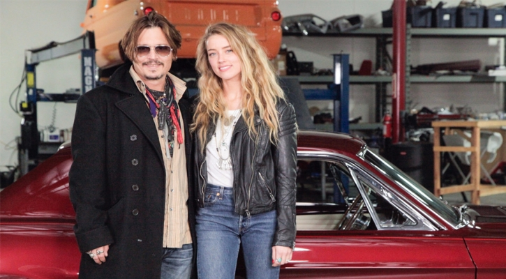 Amber Heard and husband Johnny Depp smile as they pose for a picture.