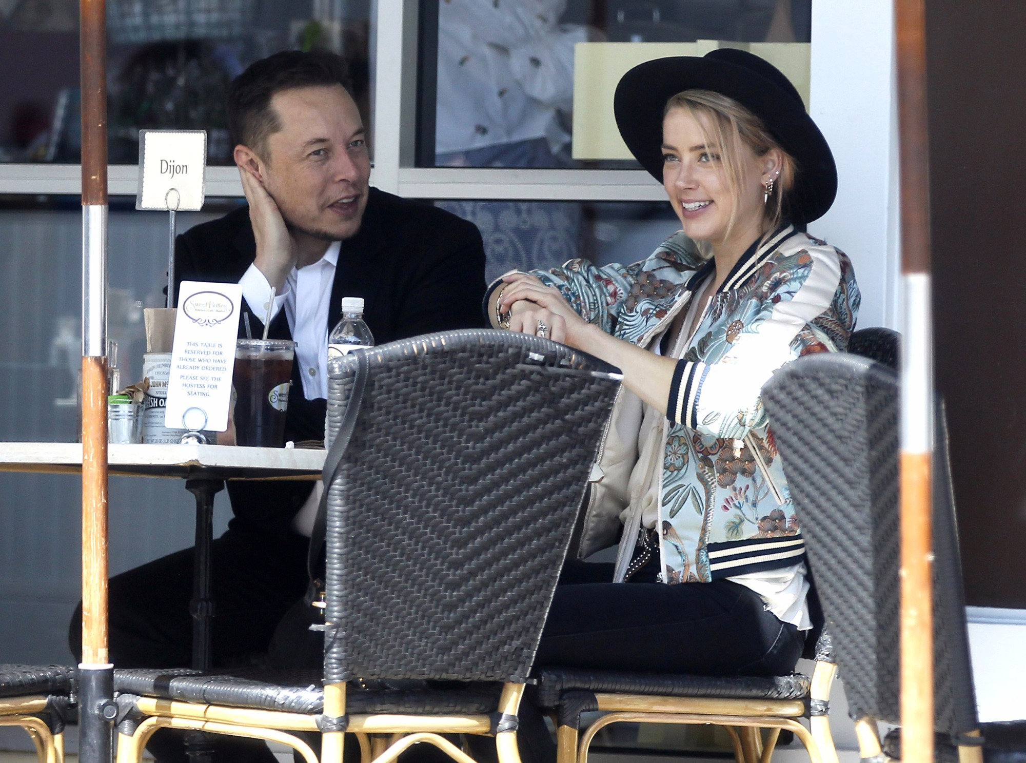 Elon Musk sitting next to Amber Heard
