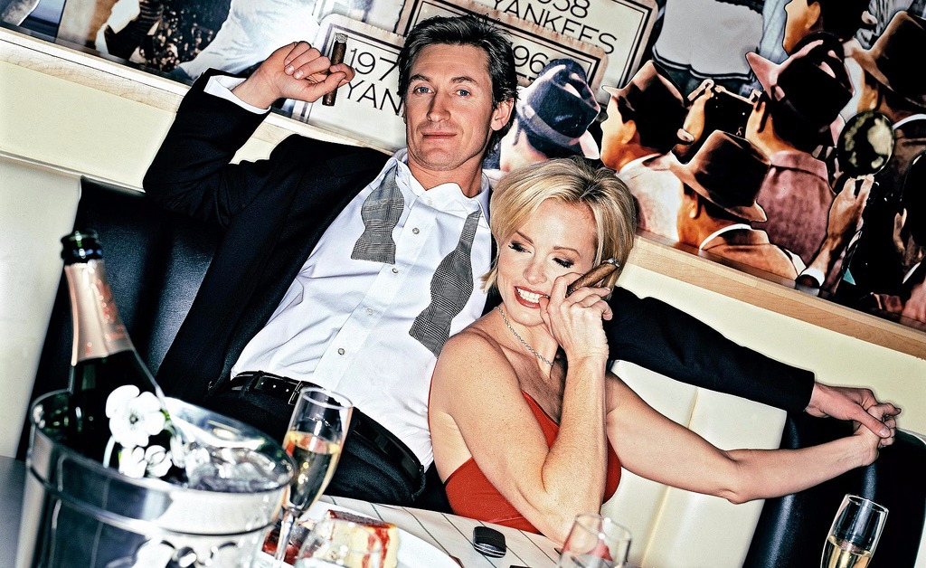Wayne Gretzky and his wife Janet Jones looking smoking hot in their sexy avatar. Janet is wearing a sleeveless red dress and is holding a cigar with a smile and Wayne Gretzky is relaxing with a champagne on the table.