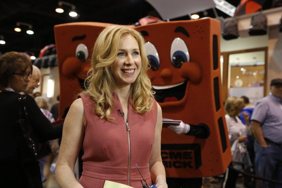 Becky Quick at Berkshire Hathaway annual shareholder meeting. There are two red cartoons behind her.
