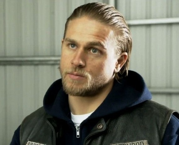Charlie Hunnam is wearing a blue hood, followed by white tees and leather half jacket