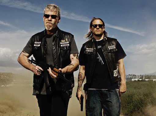 Charlie Hunnam and Ron Perlman are in biker jackets, both carrying a gun for a promotional still of Sons Of Anarchy