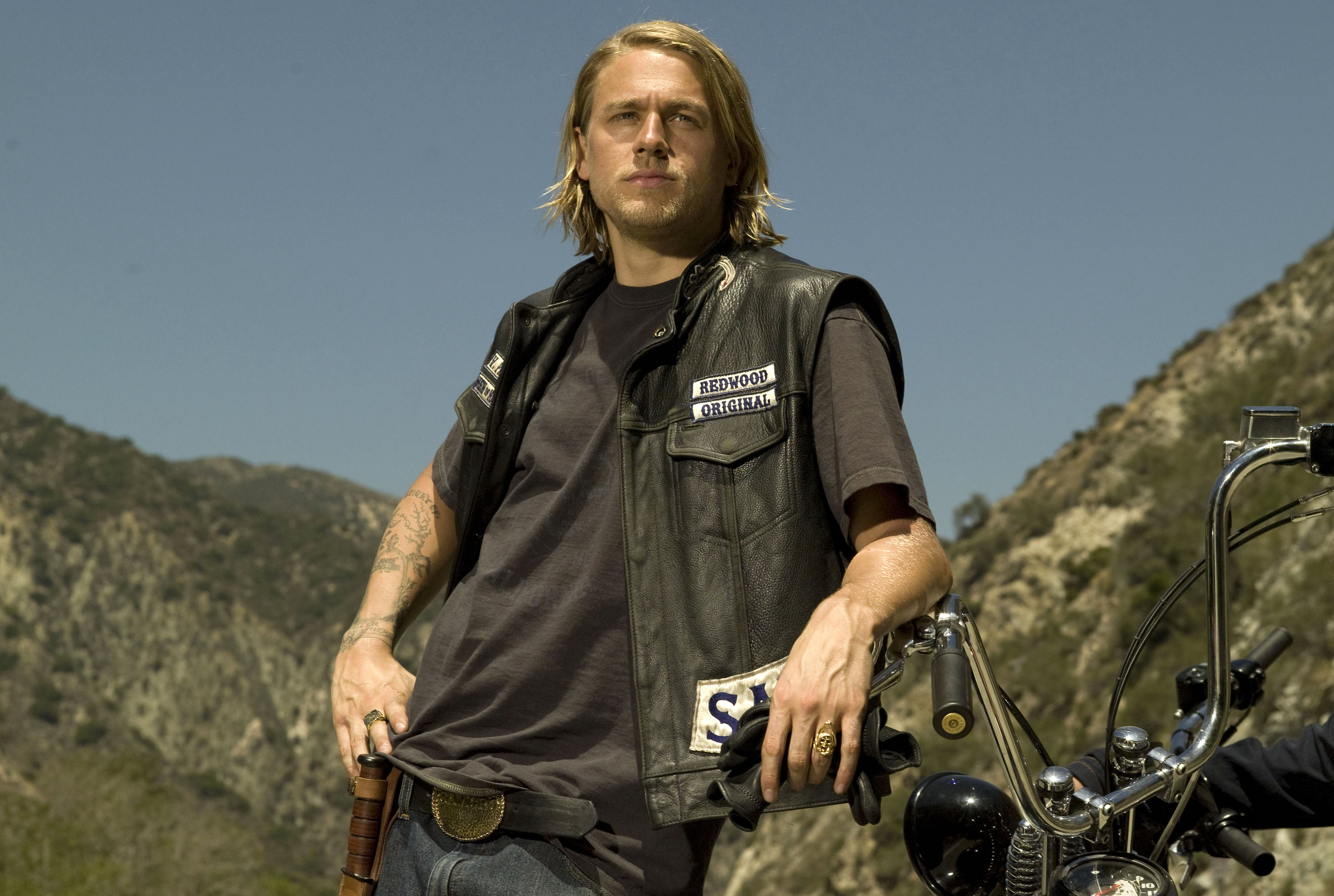 Charlie Hunnam as Jax teller is standing wearing leather jacket leaning on bike's handle