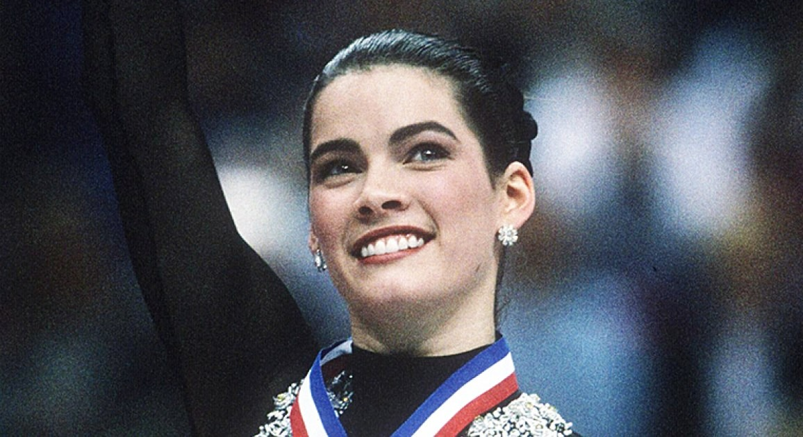 Nancy Kerrigan is celebrating a win. She is wearing a black skating outfit with a medal on her neck. Nancy is raising her hands with a big smile on her face.