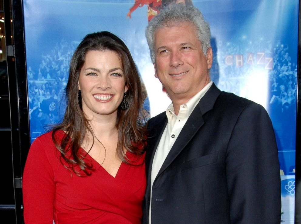 Nancy Kerrigan is standing with her husband, Jerry Solomon. The couple is attending an event. Nancy is wearing an amazing red dress while her husband is wearing a suit. The couple looks dashing in their stylish attire.