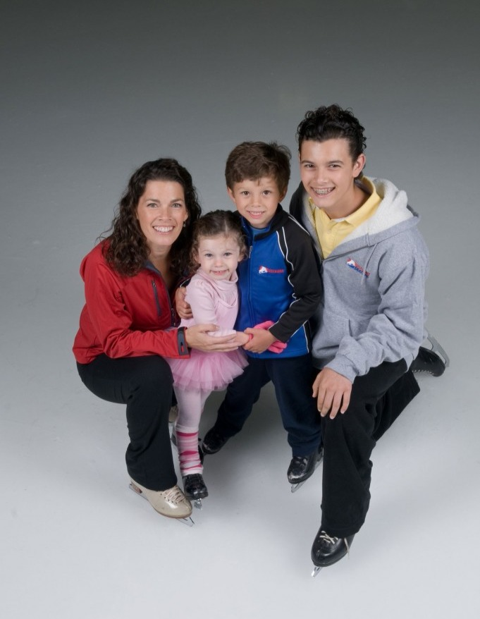 Nancy Kerrigan poses for the camera with her three children. Nancy and kids look at the camera with a smile and are wearing skate shoes. Nancy is holding the hands of her daughter.