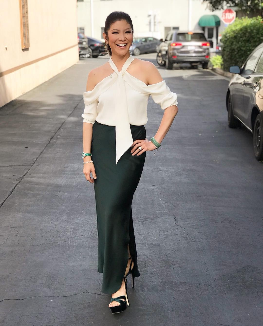 Julie Chen is standing tall in her long heels. She is looking beautiful as she smiles. Julie is wearing a white off shoulder t-shirt paired with a long avocado green skirt.