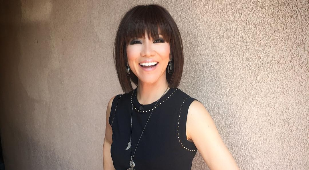Julie Chen looks hot in her black get over. She is wearing a black sleeveless skirt. She has cut her hair short and is smiling in her new look.