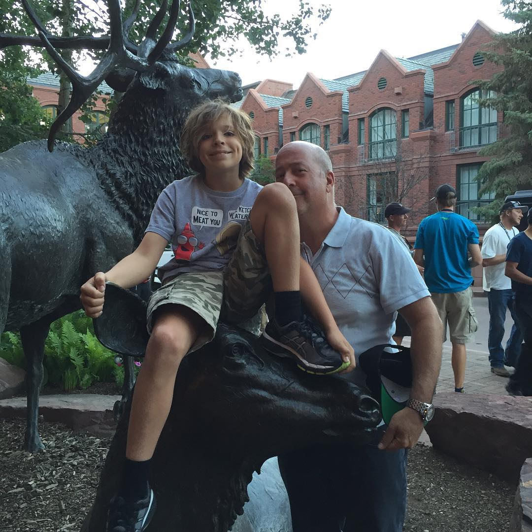 Andrew Zimmern's son Noah is sitting on a animal sculptor. Andrew is standing behind his son.