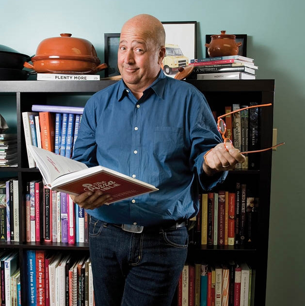 Andre Zimmern is holding an open book in one hand and his glasses on the other. There's a shelf filled with books behind him. There are two cooking pots above the shelf.