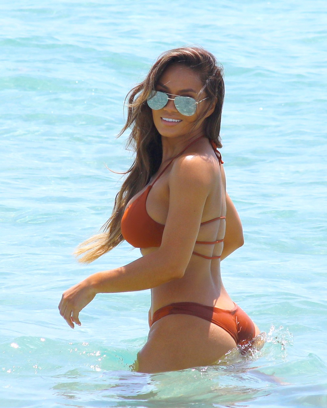 Daphne Joy looks hot in the brown bikini. She is showing off her curvaceous body taking a dip in the water.