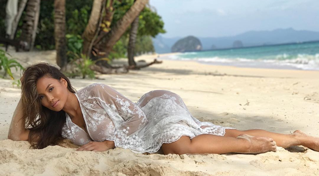 Daphne Joy lying on the beach wearing the white net dress. She look hot in white.
