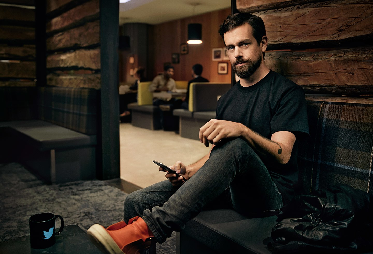 Jack Dorsey sitting on a couch with one leg on the table, there's a mug with the Twitter logo on it on the table.