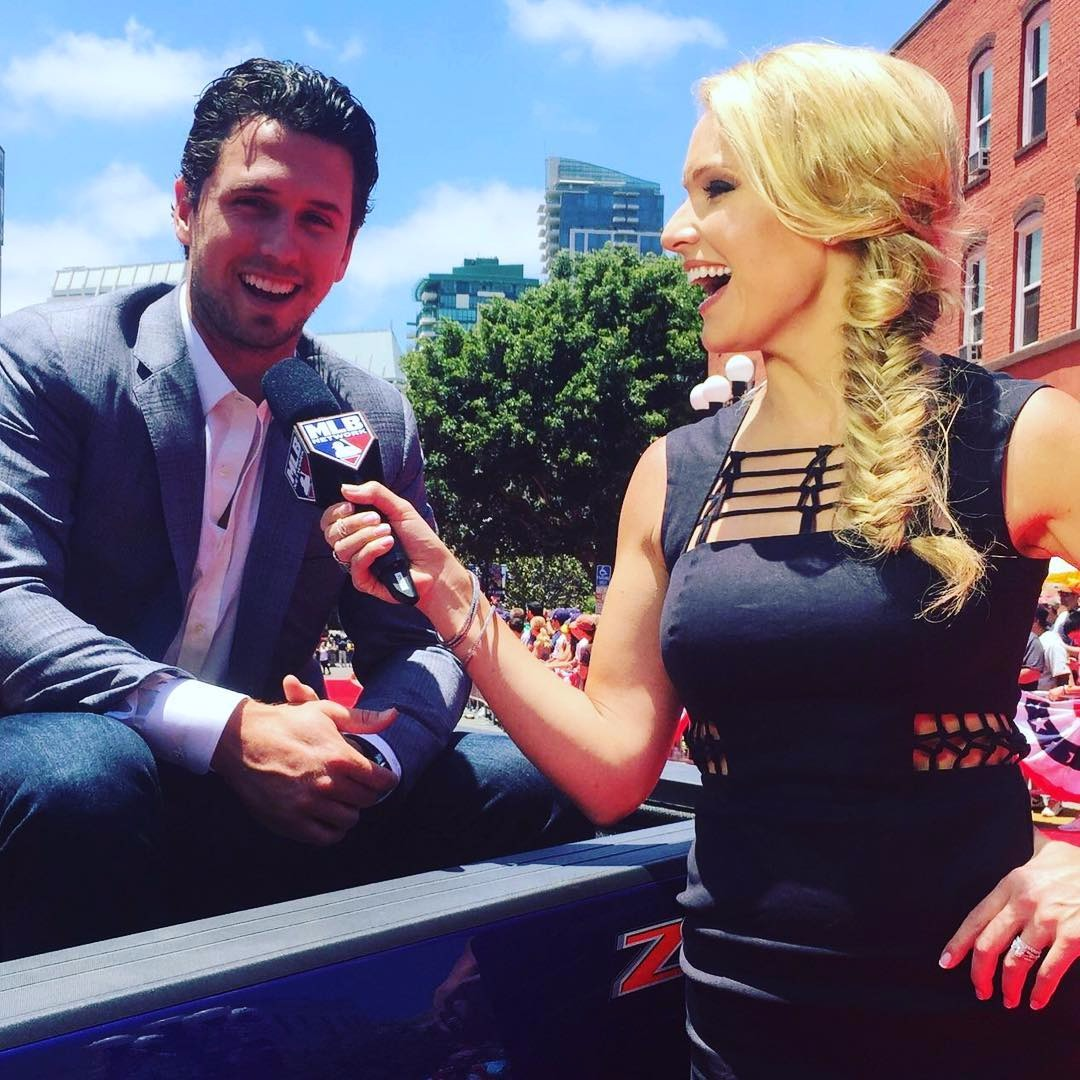 Heidi Watney is wearing a beautiful dark blue dress and interviewing Buster Posey in a red carpet event.