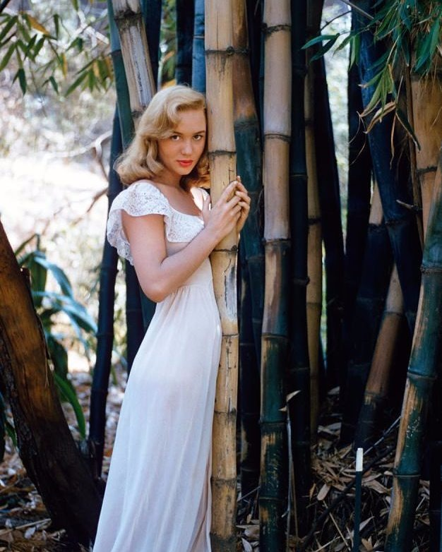 Joan Staley is wearing a white long dress and is leaning on a bamboo shoot .