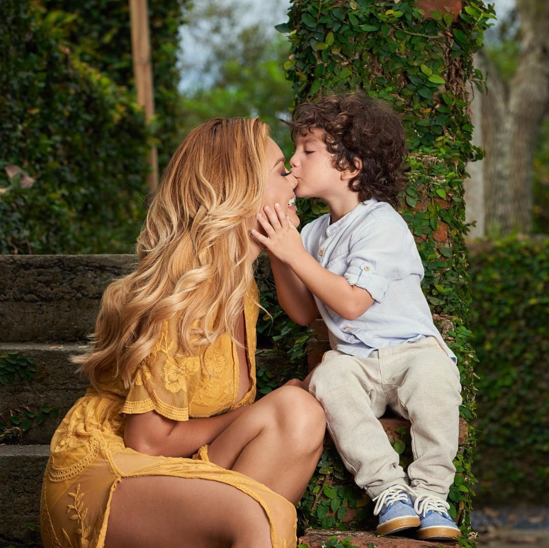 Zuleyka Rivera sitting next to son Sebastian, her son is holding her face in his hands and kissing her nose