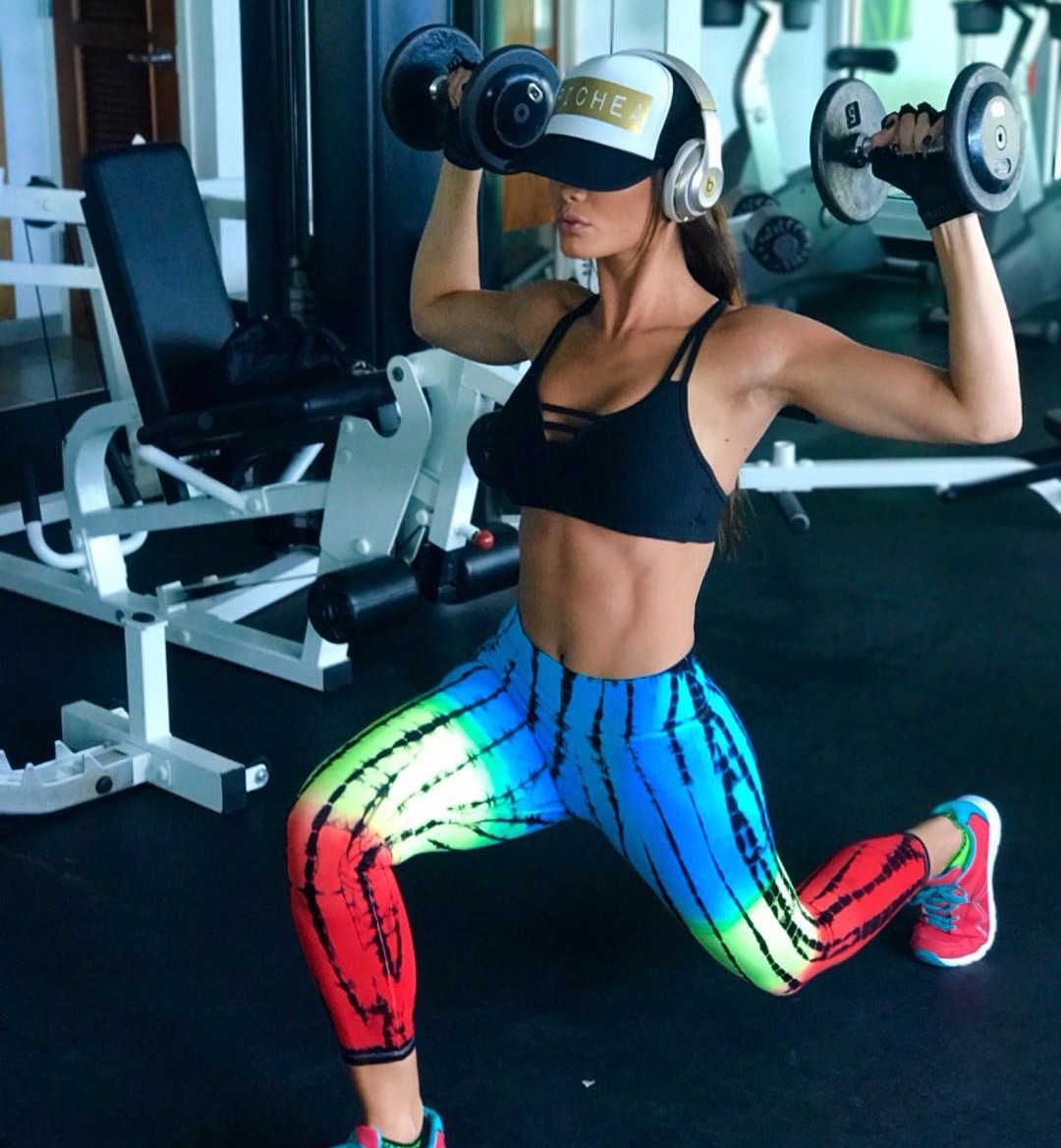 Zuleyka Rivera on one knee, she's holding a dumbbell in each hand, there's exercise equipment in the back