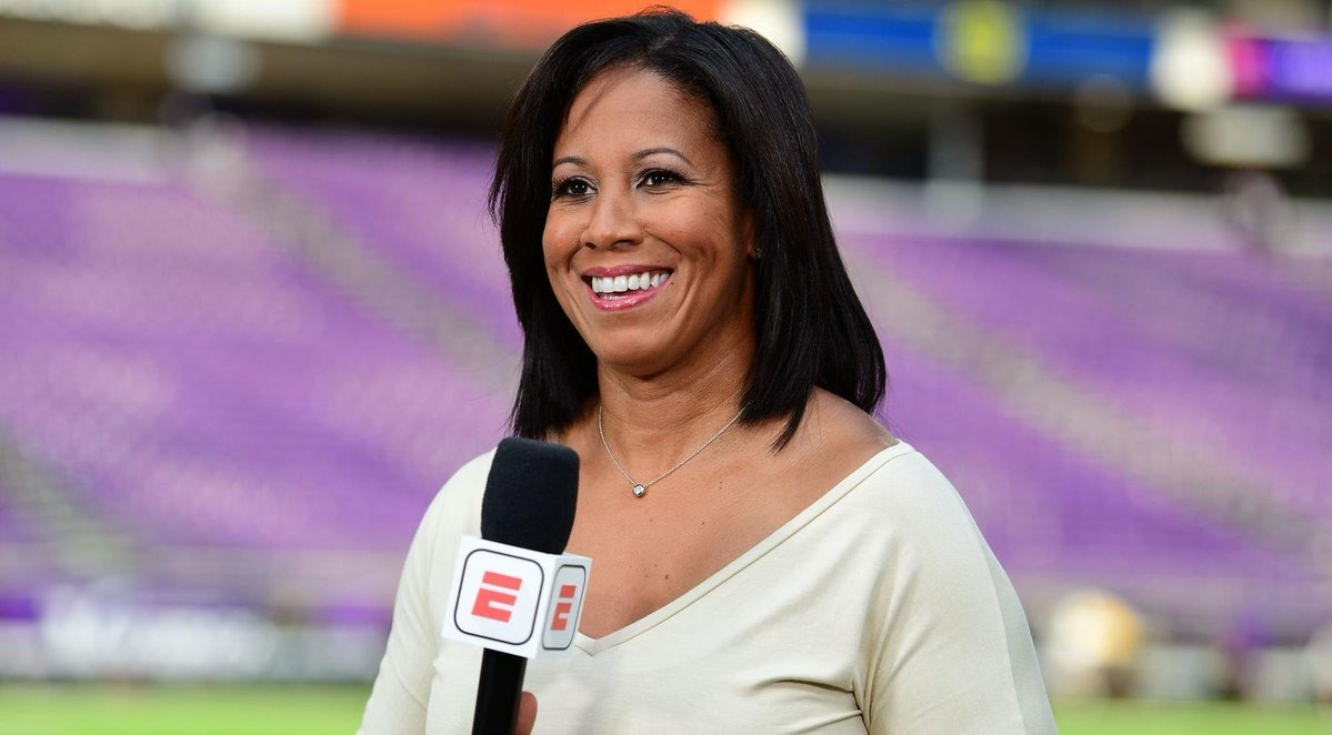 Lisa Salters is wearing a white t-shirt. She is in a stadium and holding a mic.