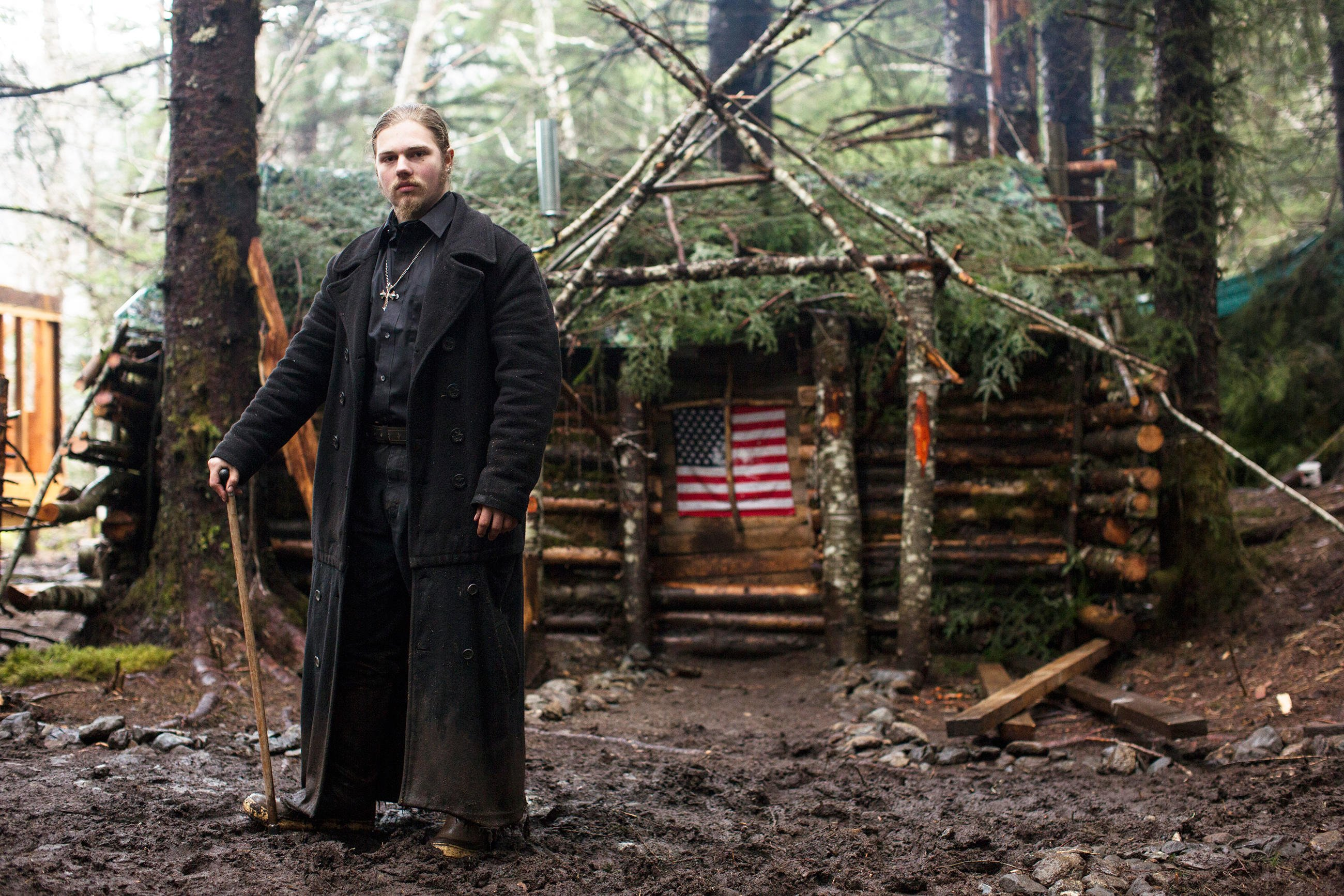 Noah Brown holding a stick in front of a hut wearing a black coat
