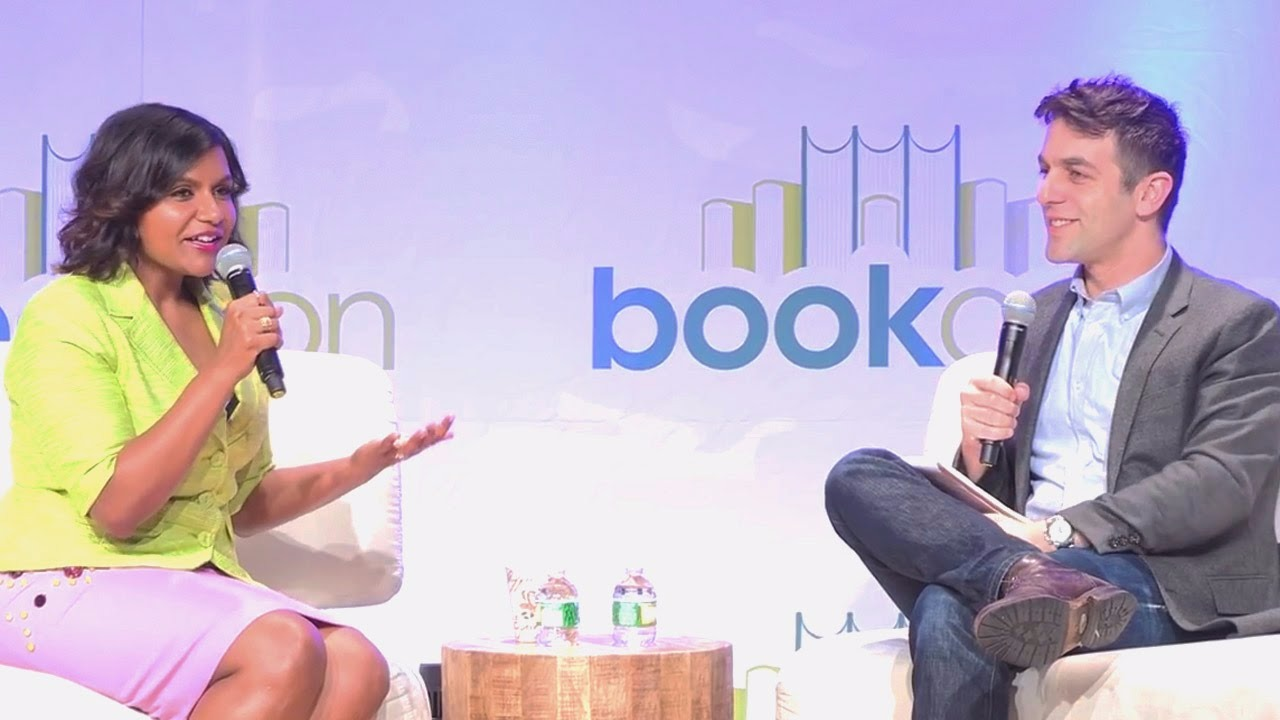 Mindy Kaling and B. J. Novak are sitting on sofas opposite to each other. Mindy is talking on a mic and B. J. Novak is also holding a mic.