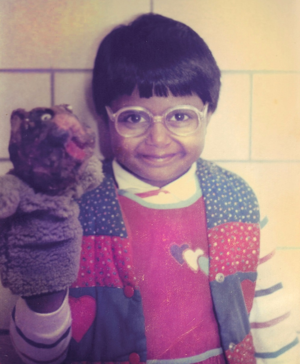 Young Mindy Kaling is smiling as she poses for a photograph. She has pixie cut and is wearing round glasses. She is also holding a puppet in her right hand.