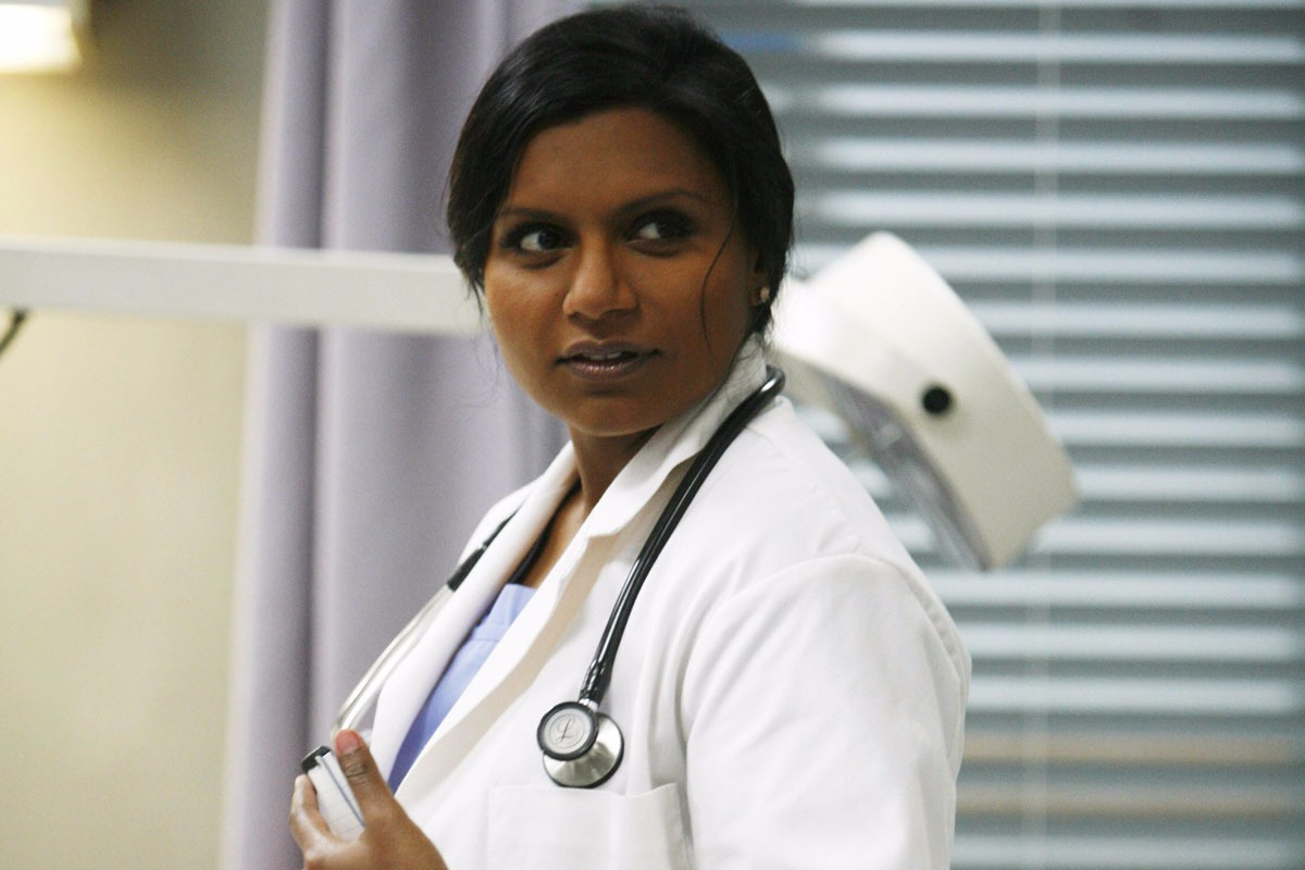 Mindy Kaling is in the get up of Dr. Mindy Lahiri from The Mindy Project. The TV show which originally aired on FOX is now showing on Hulu.