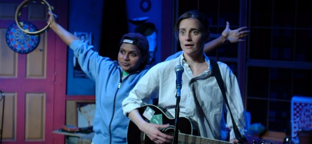 Mindy Kaling and Brenda Withers on the set of Matt & Ben. Mindy is portraying Ben Affleck while Brenda is portraying Matt Damon. Mindy is raising both her hands in the air, holding a tambourine in her right hand. Brenda is playing a guitar.