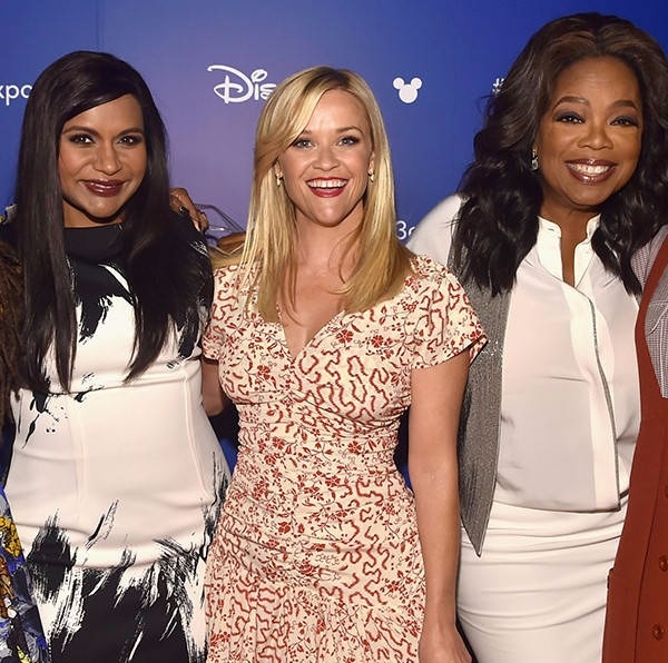Mindy Kaling, Reese Witherspoon and Oprah Winfrey are standing in the a line. All of them are smiling to the camera. There's a board of Disney in the background. The actors are working together for A Wrinkle in Time.