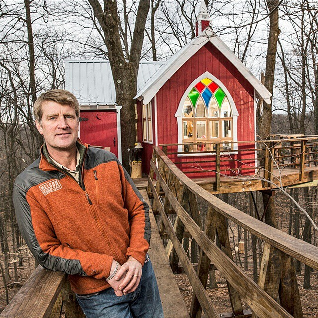 Pete Nelson leaning on the wooden plank in front of a treehouse