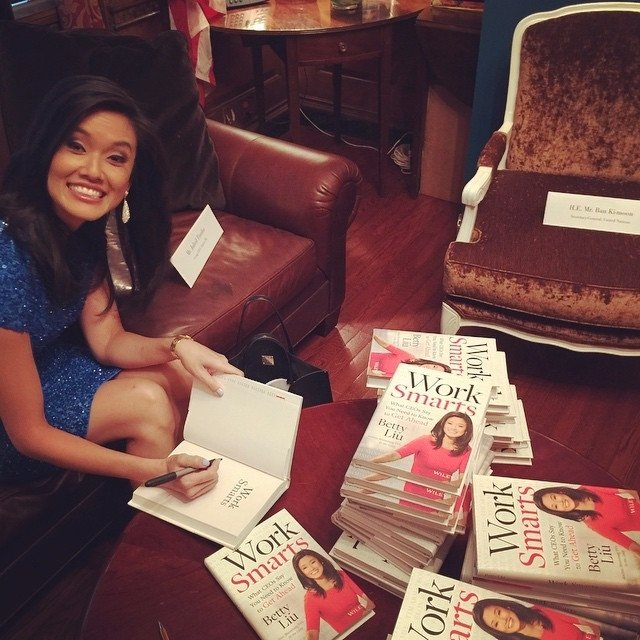 Betty Liu signing in a book and giving a huge smile to the camera